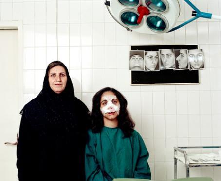 Vierekkäin vanhempi ja nuorempi nainen. Nuoremmalla naisella on kasvoissaan siteitä. Heidän yläpuolellaan on iso sairaalavalaisin.