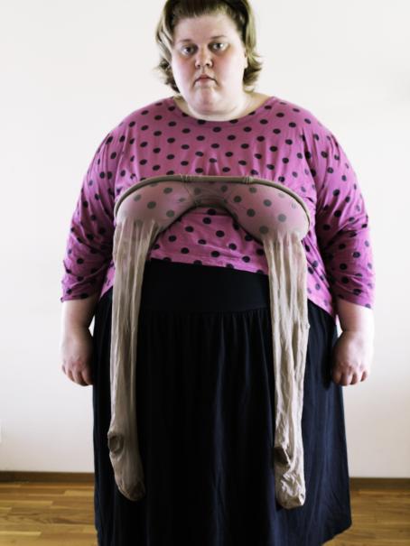 Naisen rinnoista roikkuu sukkahousut.