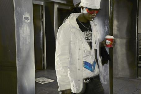 Valkoiseen farkkutakkiin pukeutunut mies seisoo Pauligin Juhlamokka-kahvikuppi kädessään. Hänellä on punaiset aurinkolasit ja valkoinen lippalakki väärinpäin päässä. Hänen takanaan on metalliset oviaukot.