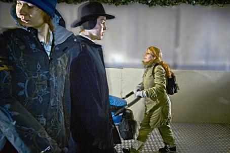 Takana nainen työntää lastenvaunuja. Etualalla on kaksi miestä, joista toinen katsoo olkansa yli taakseen.