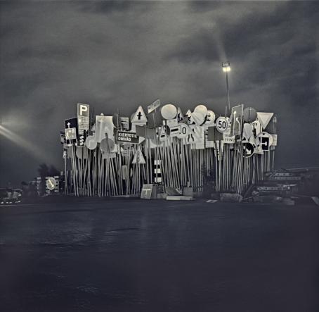 Mustavalkoisen kuvan keskellä on vierivieressä, yhdessä kasassa paljon erilaisia liikennemerkkejä. Niiden takana näkyy tummanpuhuva taivas ja niiden edessä mustaa maata.