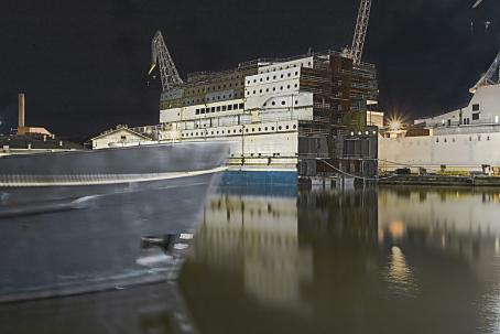 Kontteja satamassa. Taaempana näkyy nostureita. Vasemmassa reunassa on laivan etuosa.