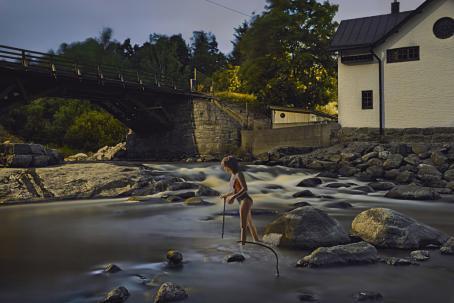 Keskellä jokea seisoo nainen uimapuku päällään. Hänellä on kädessään keppi. Joki on kivinen, ja sen rannalla on talo. Joen yli menee silta.