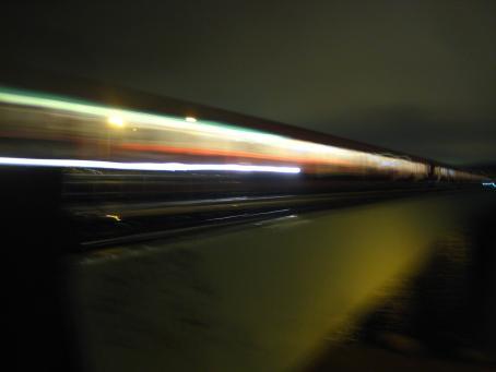 Valoviivoja jotka menevät kuvan poikki, muuten hämärää. Taaempana voi erottaa vähän junan ikkunoita.