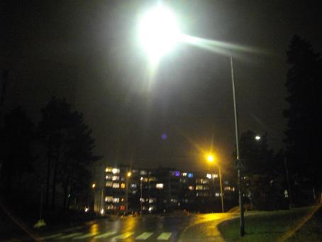 Hämärä katunäkymä. Lähimmän katuvalon valo näkyy isona pallona. Taaempana näkyy kerrostalo, jonka ikkunoista tulee valoa.