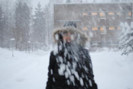 Henkilö musta talvitakki päällään ja huppu päässä, hän näkyy epäselvästi koska sataa lunta. Takana näkyy kerrostalo ja lumista maisemaa.