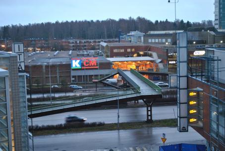 Ylhäältäpäin otetussa kuvassa näkyy autotie ja rakennuksia. Autotien yli menee kävelysilta. Isossa rakennuksessa on K-Citymarketin logo. Toisessa rakennuksessa lukee Itäkeskus ja Dinsko.