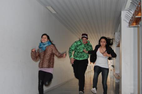 Kolme henkilöä juoksee käytävässä. Seinustalla on naulakkoja ja penkkejä.