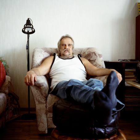 Harmaaviiksinen mies hihattomassa valkoisessa paidassa istuu nojatuolissa. Hän on nostanut jalkansa kahden rahin päälle.