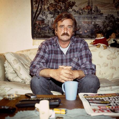 Viiksekäs mies ruudullisessa flanellipaidassa istuu sohvalla. Hänen edessään sohvapöydällä on kahvikuppi, sanomalehti, kaukosäädin, tuhkakuppi ja muuta tavaraa.