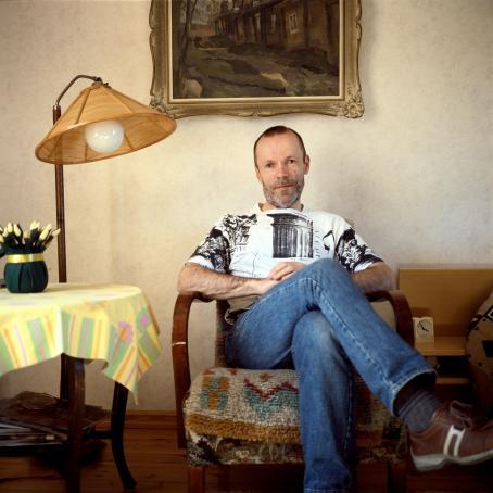 Parrakas mies istuu nojatuolissa. Hänellä on farkut ja hän on nostanut toisen jalkansa ristiin toisen päälle.