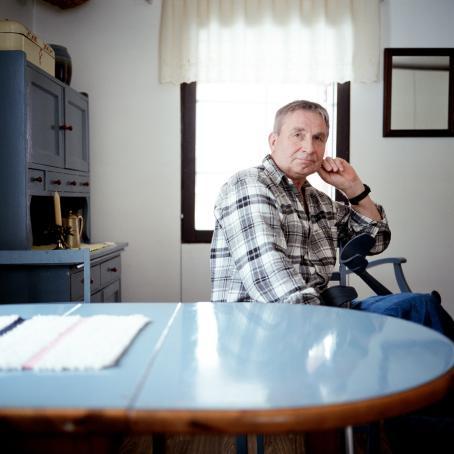 Mies istuu keittiönpöydän ääressä. Hänen syliinsä nojaavat kävelykepit.