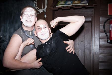 Kaksi miestä, joilla on kasvoissa jotain valkoista jauhetta tai maalia. Oikeanpuolimmainen nojaa vasemmanpuoleiseen ja on koukistanut kätensä kuin esitelläkseen hauislihaksiaan.