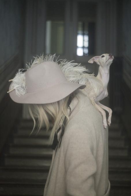 Rappukäytävässä nainen, jonka kasvoja ei näy hiusten takaa. Hänellä on vaalea takki ja iso vaaleanpunainen hattu jossa on sulka, ja hänen olkapäällään on koira joka katsoo ylöspäin.