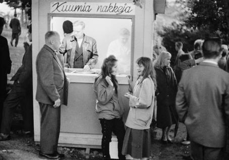 """Kioski, jonka seinässä lukee """"kuumia nakkeja"""". Kioskin edessä seisova vanhempi mies on tilaamassa ja hänen vieressään seisoo kaksi nuorta tyttöä. Taustalla näkyy muita ihmisiä."""