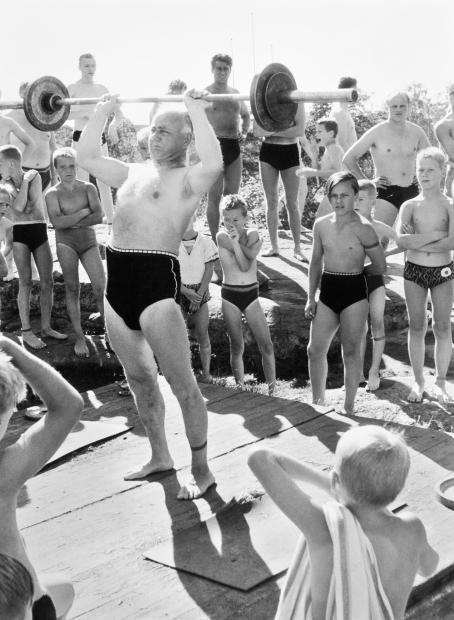 Keskellä vanhempi mies uimahousut jalassa nostaa painoja. Hänen ympärillään on paljon uima-asuisia miehiä ja poikia.