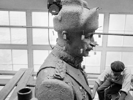 Mannerheimin veistos työstövaiheessa. Patsaasta roikkuu lappusia ja alareunassa näkyy taiteilija.