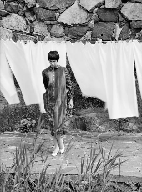 Mustahiuksinen nuori nainen raidallisessa mekossa seisoo pyykkinarulla roikkuvien valkoisten lakanoiden edessä.