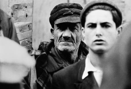Kaksi henkilöä, edessä epäselvemmin nuorempi mies ja takana selvemmin vanhempi mies jolla on uurteiset kasvot.