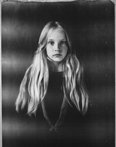 Mustavalkoisessa kuvassa tyttö, jolla on pitkät hiukset ja kaulassa partiolaisten huivi.
