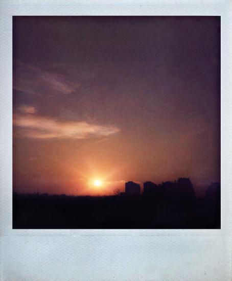 Aurinko on alhaalla ja taivas on oranssi ja ylempänä violetti. Kerrostalot näkyvät kaukana mustana siluettina taivasta vasten.