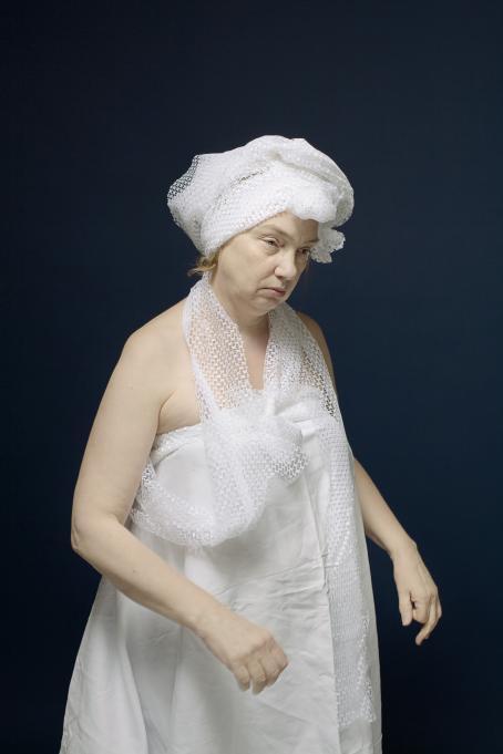 Nainen jolla on valkoisesta kankaasta tehty mekko, kaulassa huivi ja päässä samasta kankaasta kietaistu päähine.