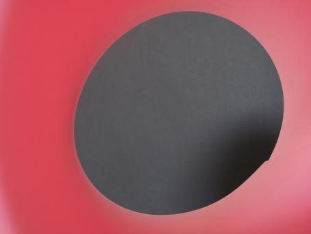 Vaaleanpunaisella taustalla harmaansävyinen ympyrä, jonka yhdellä reunalla harmaa tummenee mustaksi.