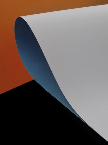 Tausta on yläosasta oranssia ja alaosasta tummanpunaruskeaa. Taustan edessä on kaksinkerroin taitettu paperi, ja taitoskohtaan tulee sininen soikea muoto.
