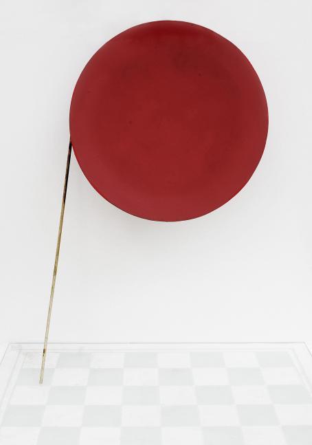 Vaaleaa taustaa vasten iso punainen ympyrä, jonka vasemmalta puolelta lähtee alaspäin suora keppi tai tikku. Alhaalla vaaleaa shakkilautakuvioista lattiaa.