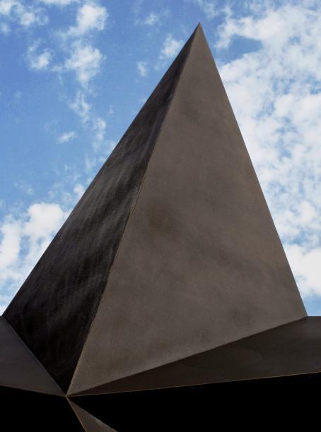 Ruskea, korkea, sileäpintainen pyramidin muotoinen rakennus, jonka alareunasta lähtee tasoja eri suuntiin. Rakennuksen takana näkyy sinistä taivasta ja valkoisia pilviä.
