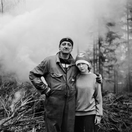 Mustavalkoisessa kuvassa vanhempi mies jonka kainalossa on nuorempi nainen. Miehellä on työhaalarit päällä, takana on risuja joista tulee savua.
