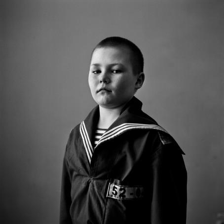 Mustavalkoisessa kuvassa on nuori, lyhythiuksinen poika.