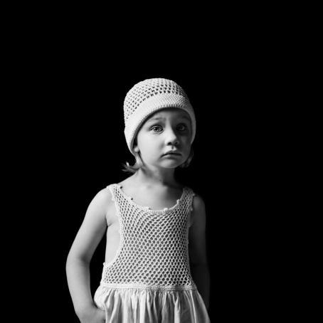 Mustavalkoisessa kuvassa mustaa taustaa vasten pieni tyttö valkoisessa mekossa ja samanlaisessa pipossa. Pipon alta näkyy kiharoita.