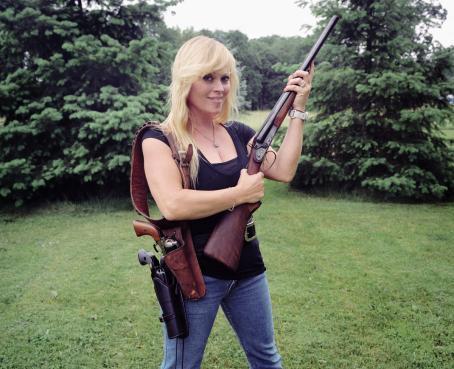 Vaaleahiuksinen nainen seisoo ulkona nurmikolla ja pitelee käsissään kivääriä.