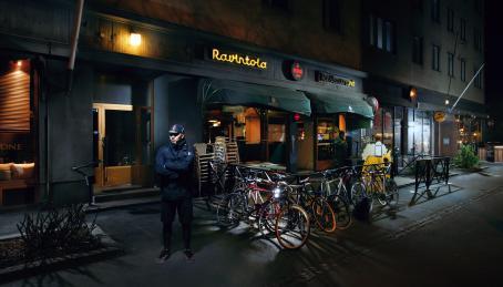 Hämärällä kadulla mies seisoo kädet puuskassa ravintolan edessä. Ravintolassa on terassi, ja terassin aitoihin on kiinnitetty polkupyöriä.