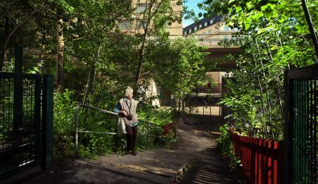 Vanha nainen nojaa kävelytiellä tai polulla olevien portaiden kaiteeseen. Ympärillä on vihreää puistikkoa, taaempana näkyy rakennuksia ja tien yli menevä silta.
