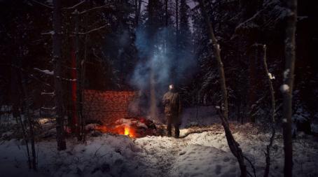 Mies seisoo lumisessa metsässä muki kädessään ja katsoo ylöspäin. Hänen vieressään palaa nuotio. Nuotion vieressä on puiden väliin pingotettu kangas.