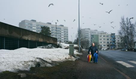 Harmaassa katumaisemassa jalkakäytävällä seisoo mies kahden pienen lapsen kanssa. Tien pientareella on lunta, taaempana näkyy kerrostaloja ja taivaalla lentelee paljon lokkeja.