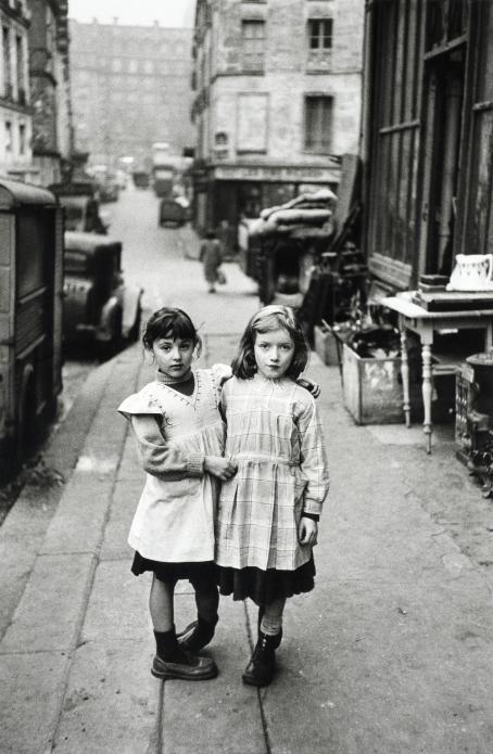 Mustavalkoisessa kuvassa kaksi pientä tyttöä kaupungin kadulla. Toinen pitää kättä toisen harteilla.