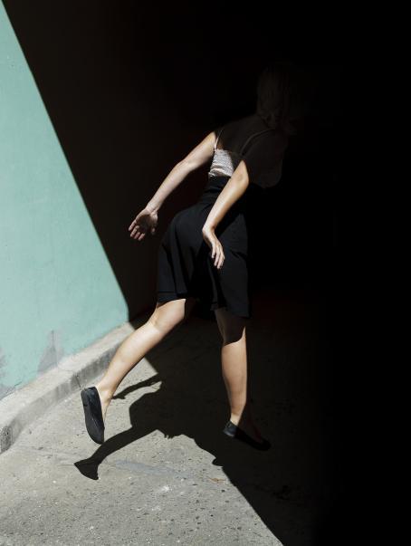 Kuvan poikki menee varjon raja, niin että osa kuvasta on valoisaa ja osa mustaa. Keskellä juoksee henkilö, joka on osittain varjossa ja osittain valossa.