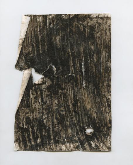 Suorakulmion muotoinen tumma palanen paksua paperia tai jotain muuta materiaalia, siinä on tumma pinta ja se on repeytynyt monesta kohdasta.