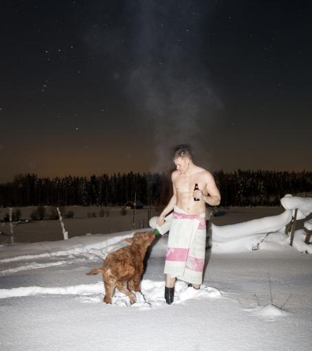 Lumihangessa seisoo mies ilman paitaa pyyhe vyötärön ympärillä, kaljapullo kädessä. Hänen vieressään on vasikka, jolle hän juottaa pullosta jotain. Miehestä nousee höyryä. Taustalla näkyy lumista maisemaa ja tähtitaivas.