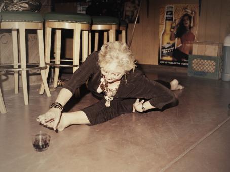 Lattialla nainen on spagaattiasennossa. Hänen edessään on lasi jossa on jotain juotavaa.