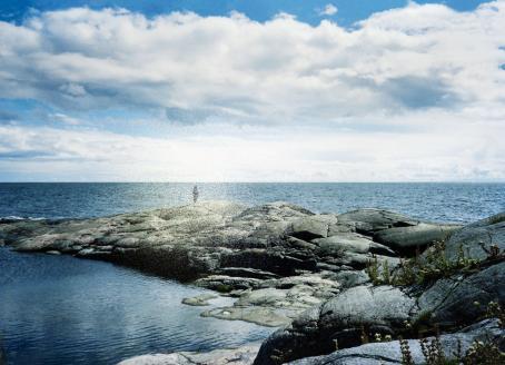 Rantakallioilla seisoo ihminen, takana näkyy aava ulappa. Taivaalla on isoja valkoisia pilviä.