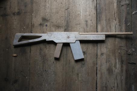 Roskaisella lautalattialla on puusta tehty ase.