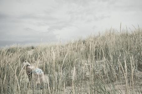 Hiekkarannan kaislikossa kaislojen takana on nainen uimapuku päällä nelinkontin.