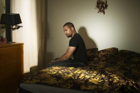 Tummaihoinen mies istuu sängyn reunalla. Sängylle tulee kaistale valoa. Seinällä sängyn yläpuolella roikkuu unisieppari.