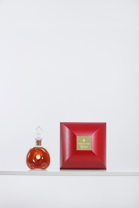 Valkoista taustaa vasten valkoisella tasolla on punainen laatikko ja sen vieressä koristeellinen läpinäkyvä pullo, jossa on punaista nestettä. Laatikon keskellä on kultainen laatta jossa lukee Louis XIII.