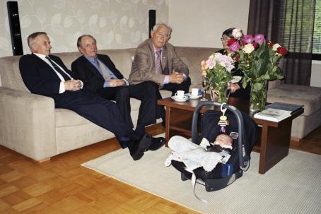 Sohvalla istuu kolme vanhaa miestä ja yksi vanha nainen. Sohvapöydällä on kahvikuppeja ja lautasia ja maljakoissa kukkia. Nainen jää osittain kukkien taakse. Pöydän edessä lattialla nukkuu vauva turvakaukalossa.