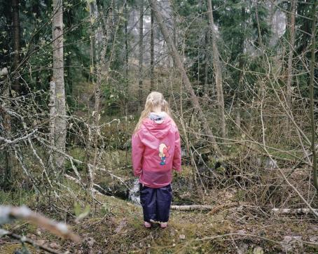 Metsässä pienen puron tai lammikon edessä seisoo selin tyttö, jolla on pitkissä, vaaleissa hiuksissa saparot ja pitkä vaaleanpunainen sadetakki.